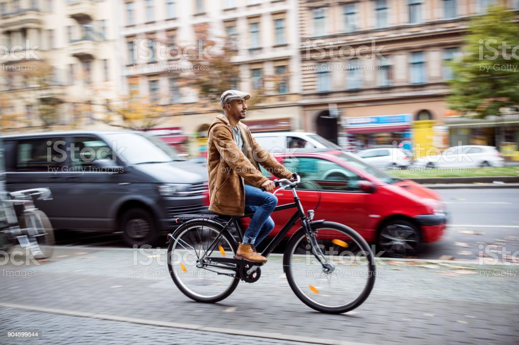 Man cycling on street in city during winter stock photo