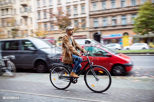 Man Cycling On Street In City During Winter Stock Photo & More Pictures of 30-34 Years