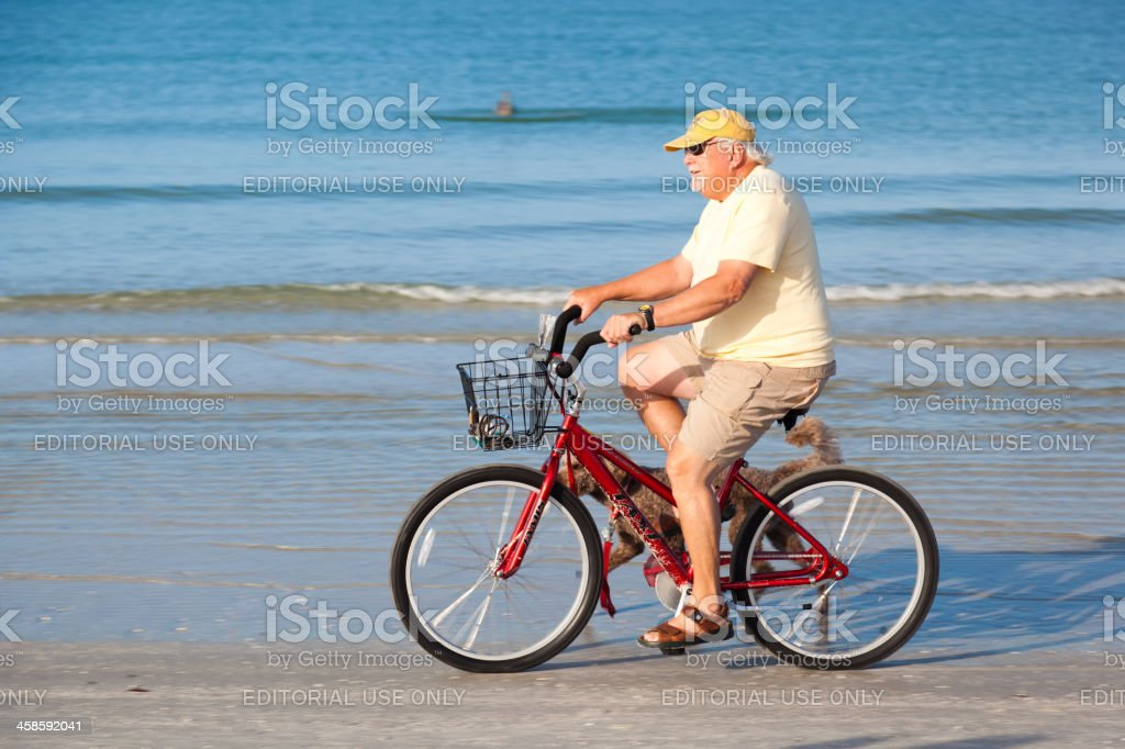 Man cycling on the beach with his dog royalty-free stock photo