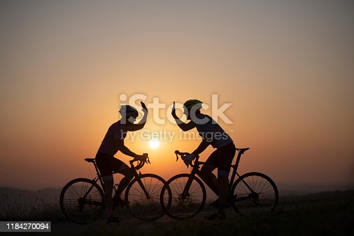 Happy athlete men on racing bicycle on sunset.