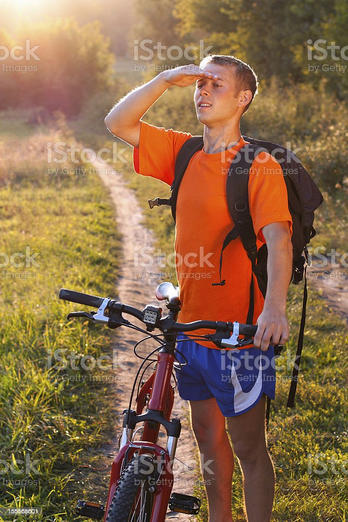Man cyclist carefully scrutinizes the direction royalty-free stock photo