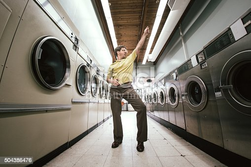 A man in 1980's style does his laundry at an old school laundromat, dancing disco style in the walkway between the washers and dryers while waiting for his clothing to finish drying.  Horizontal fisheye image with copy space.