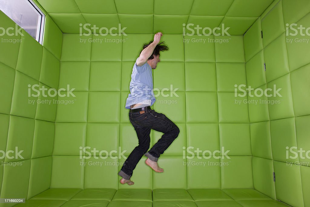 Man dancing in padded room stock photo