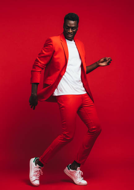 Man dancing on red background Full length od handsome young african man dancing on red background. Man in stylish red outfit showing some dance moves. studio stock pictures, royalty-free photos & images