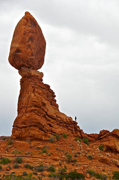 Man, dark sky, Balanced Rock, Arches National Park, Utah, USA stock photo