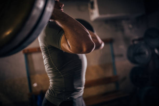 Man deadlifting barbell in gym stock photo