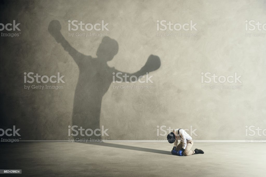 man defeated by his shadow boxing stock photo