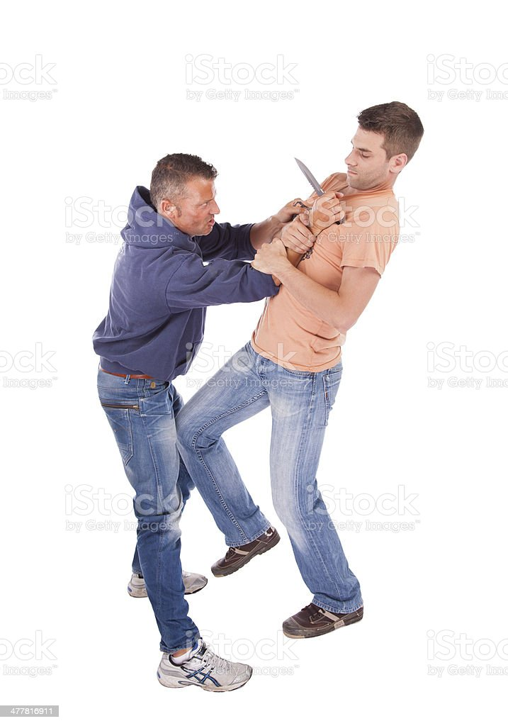 Man defending against knife attack stock photo