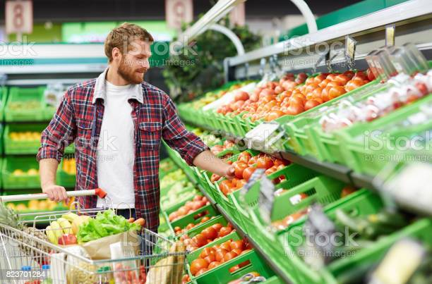 Man defining quality of tomato in supermarket picture id823701284?b=1&k=6&m=823701284&s=612x612&h=at8nuv7aysxl 4dccybev2y6muz91dn7m9woql4e8r0=