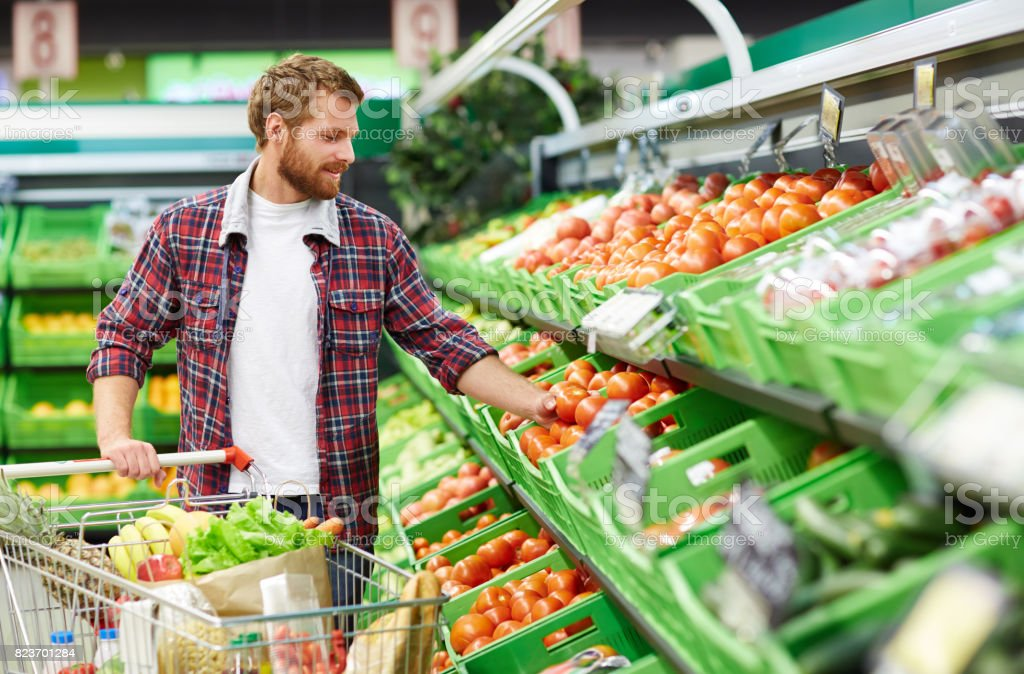 Man defining quality of tomato in supermarket стоковое фото