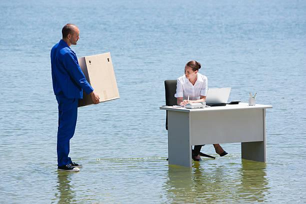 mann liefern pappkarton, frau am schreibtisch auf dem wasser - was bringt unglück stock-fotos und bilder