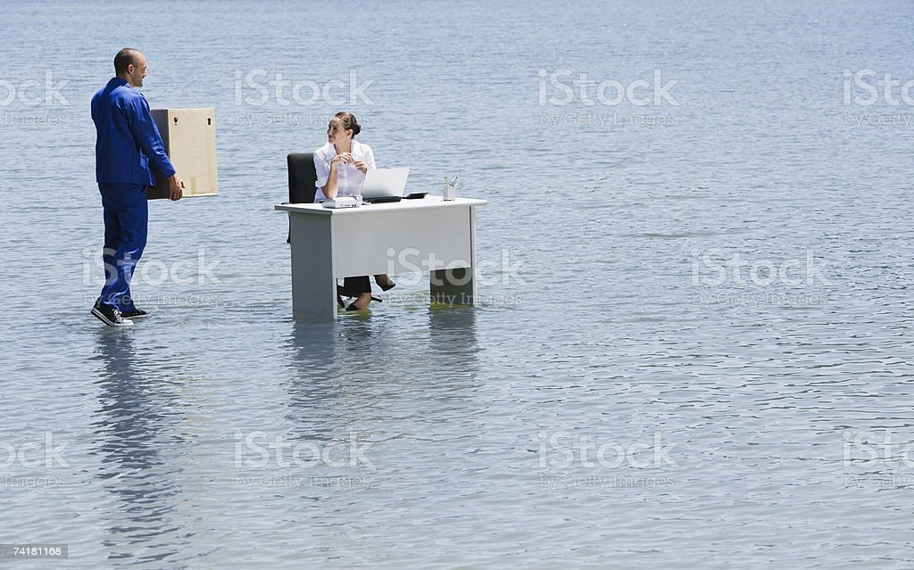 Man delivering cardboard box to woman at desk on water royalty-free stock photo
