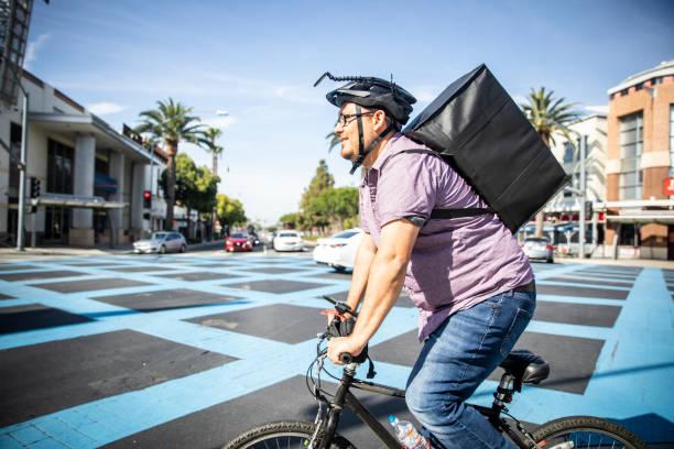 Mann liefert Essen auf Fahrrad in Busy City – Foto