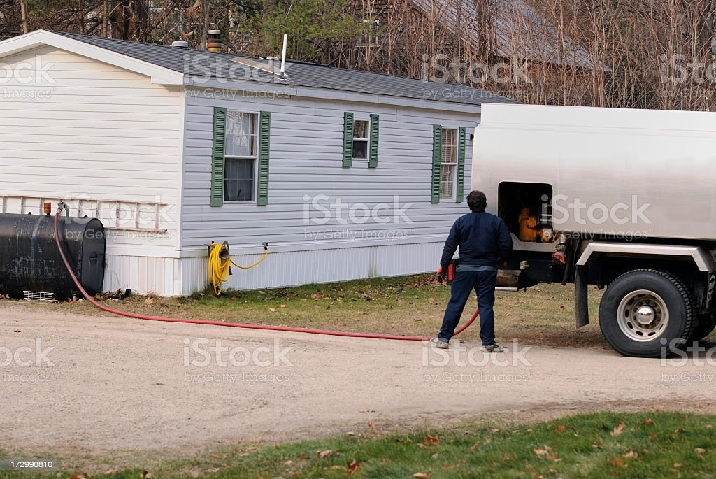 Man delivering fuel to countryside home stock photo