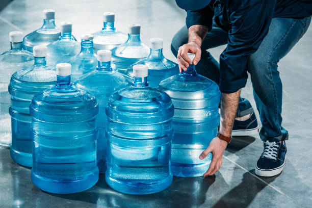 Man delivering large bottles with drinking water Man delivering large bottles with drinking water gallon stock pictures, royalty-free photos & images