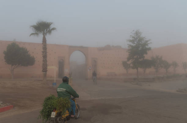 Man delivers fresh produce in early morning mist at the Bab Aylan gateway entrance to the Medina in Marrakesh stock photo