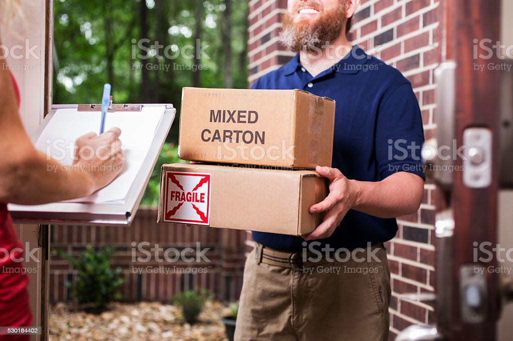 One mid-adult man wearing blue uniform delivers packages to customer...