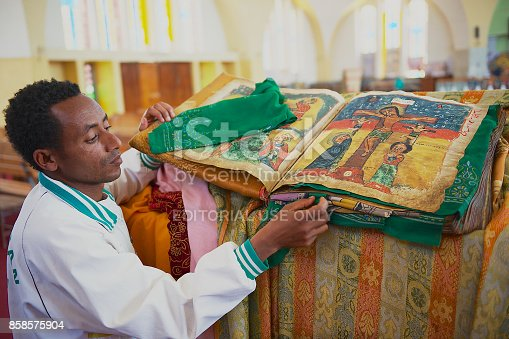 istock Man demonstrates ancient Bible in Amharic language in the church of Our Lady Mary of Zion, the most sacred place for all Orthodox Ethiopians in Aksum, Ethiopia. 858575904