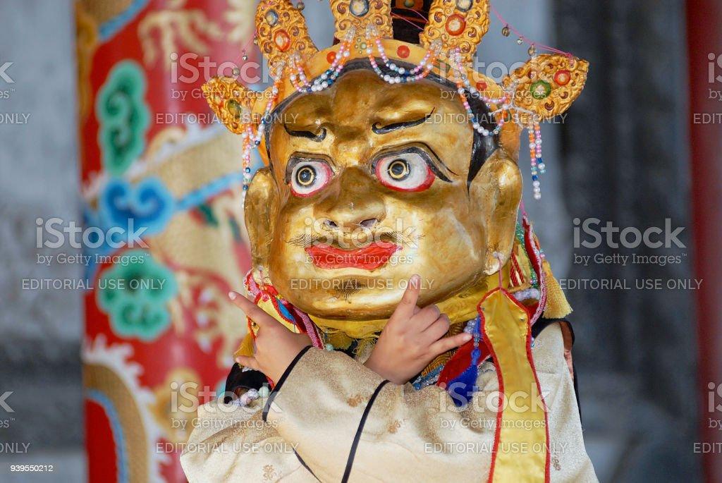 Man demonstrates traditional shaman's mask and costume in Ulaanbaatar, Mongolia. stock photo