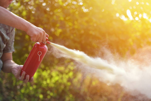 A man demonstrating how to use a fire extinguisher A man demonstrating how to use a fire extinguisher extinguishing stock pictures, royalty-free photos & images