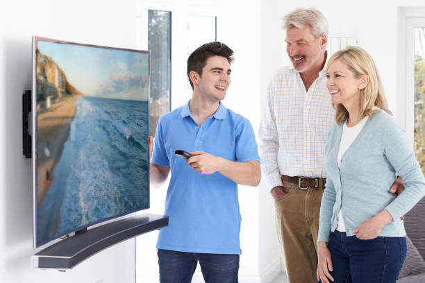 Man Demonstrating New Television To Mature Couple At Home Man Demonstrating New Television To Mature Couple At Home 4k resolution stock pictures, royalty-free photos & images