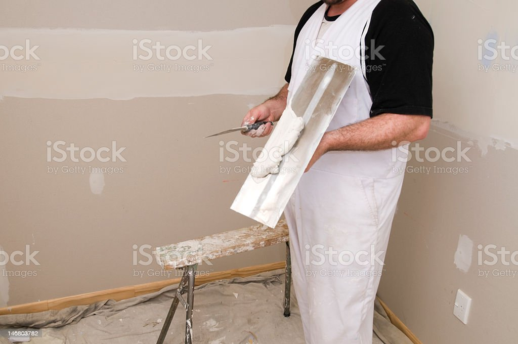 Man demonstrating plastering in a room under renovation royalty-free stock photo