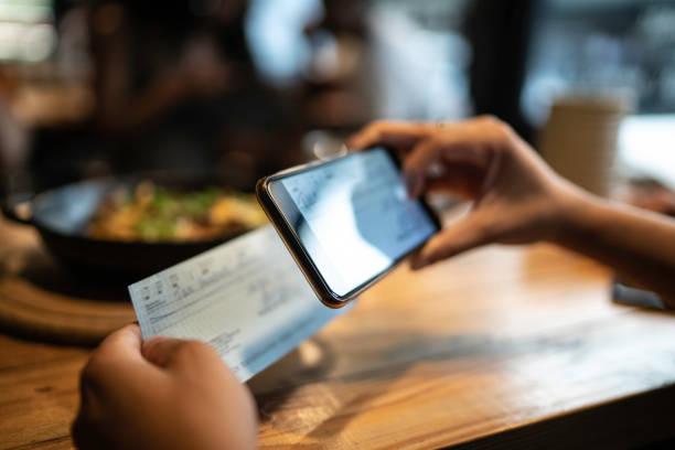 uomo deposita assegno per telefono nel ristorante - dispositivo informatico portatile foto e immagini stock
