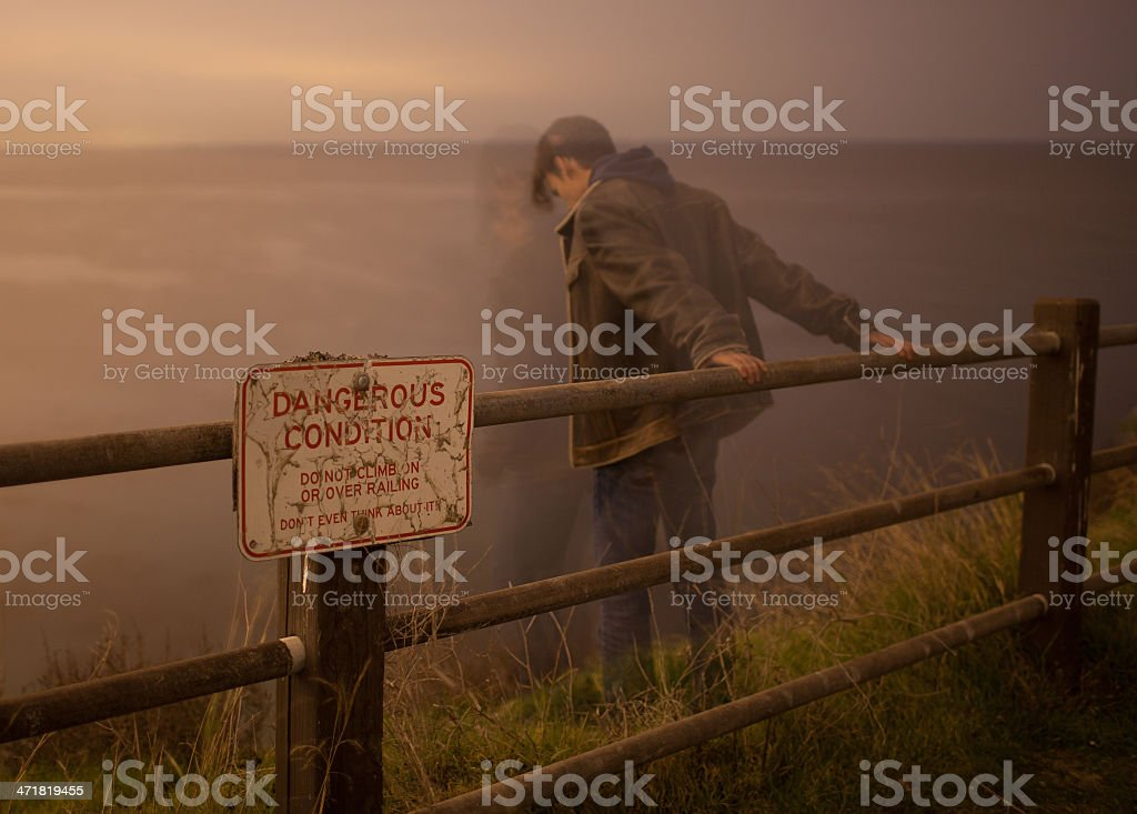 A man depressed looking over the edge of a cliff stock photo