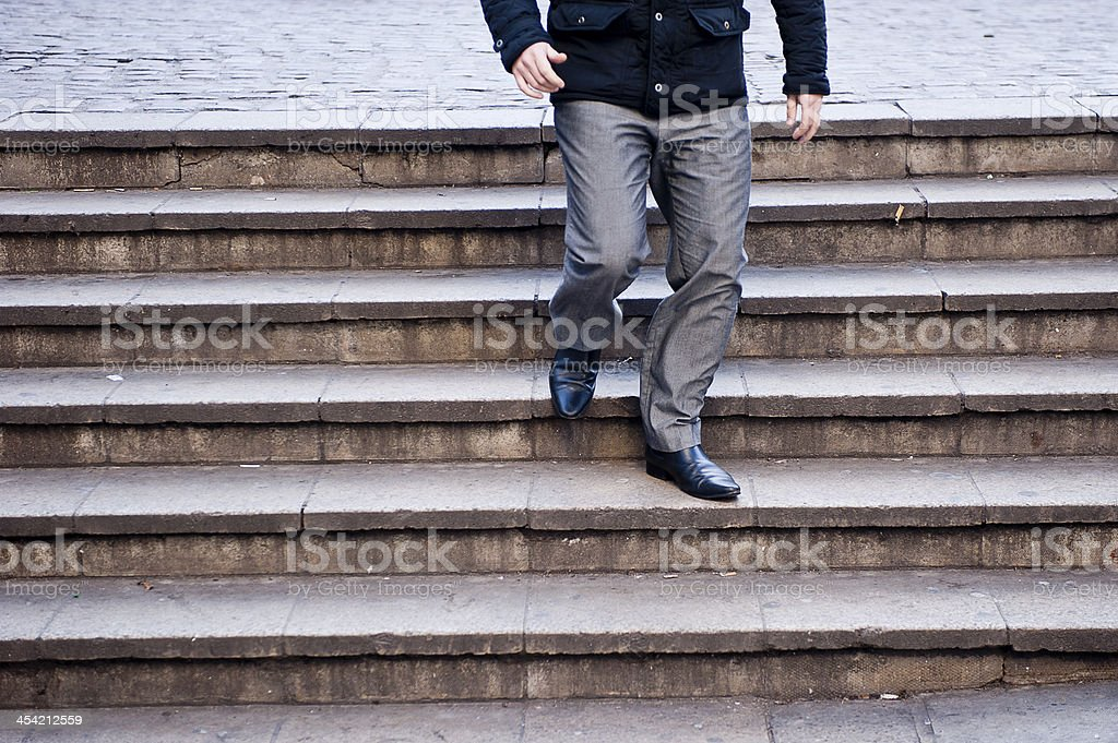 Man descending stairs stock photo