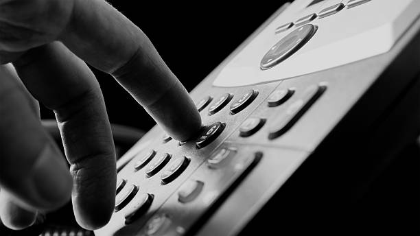 Man dialing out on a land line telephone Close up of the fingers of a man dialing out on a land line telephone pressing the number keys on the keypad in a communications concept. bingo caller stock pictures, royalty-free photos & images