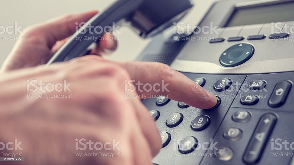 Man dialling out on a landline telephone stock photo