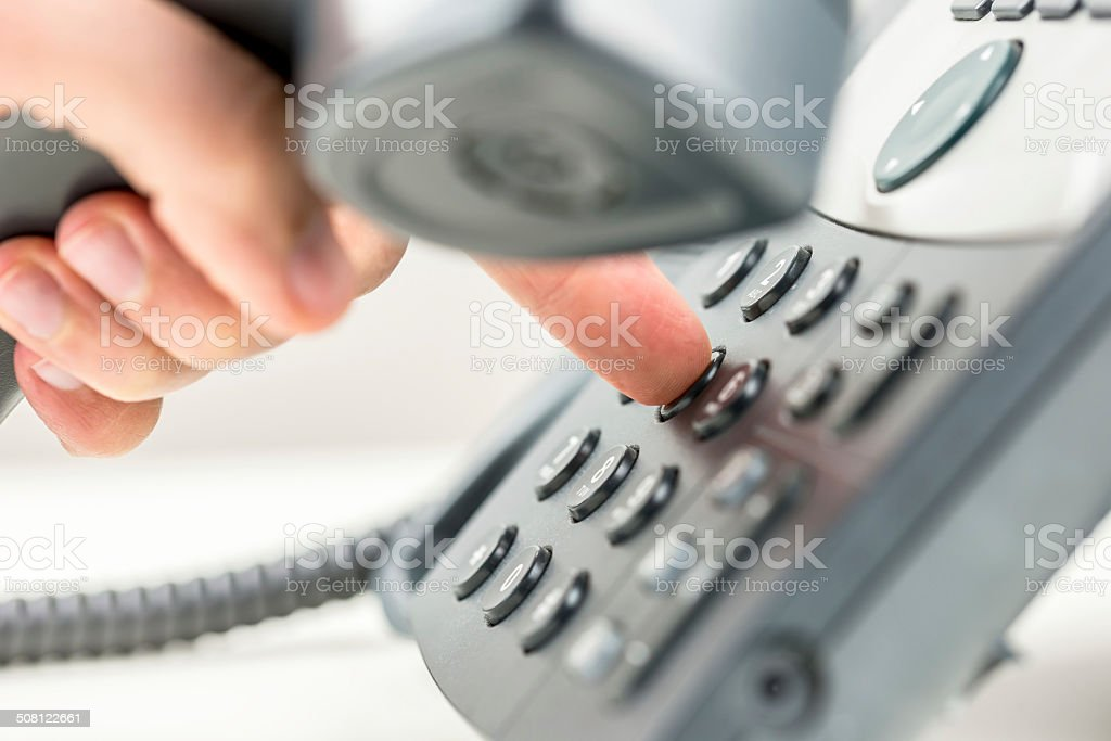 Man dialling out on a telephone stock photo