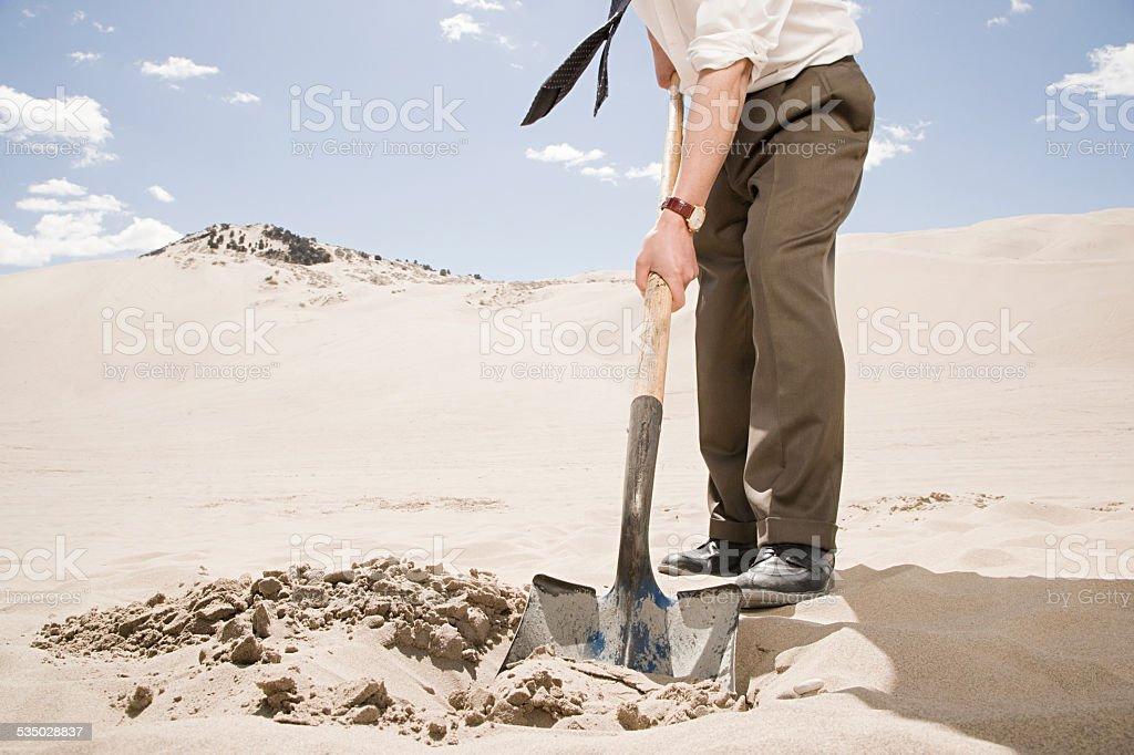 Man digging in desert stock photo