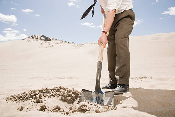 man digging in desert - gömülü stok fotoğraflar ve resimler