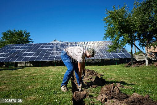 istock Man digging the ground with a showel in front of solar pannels. 1008870108
