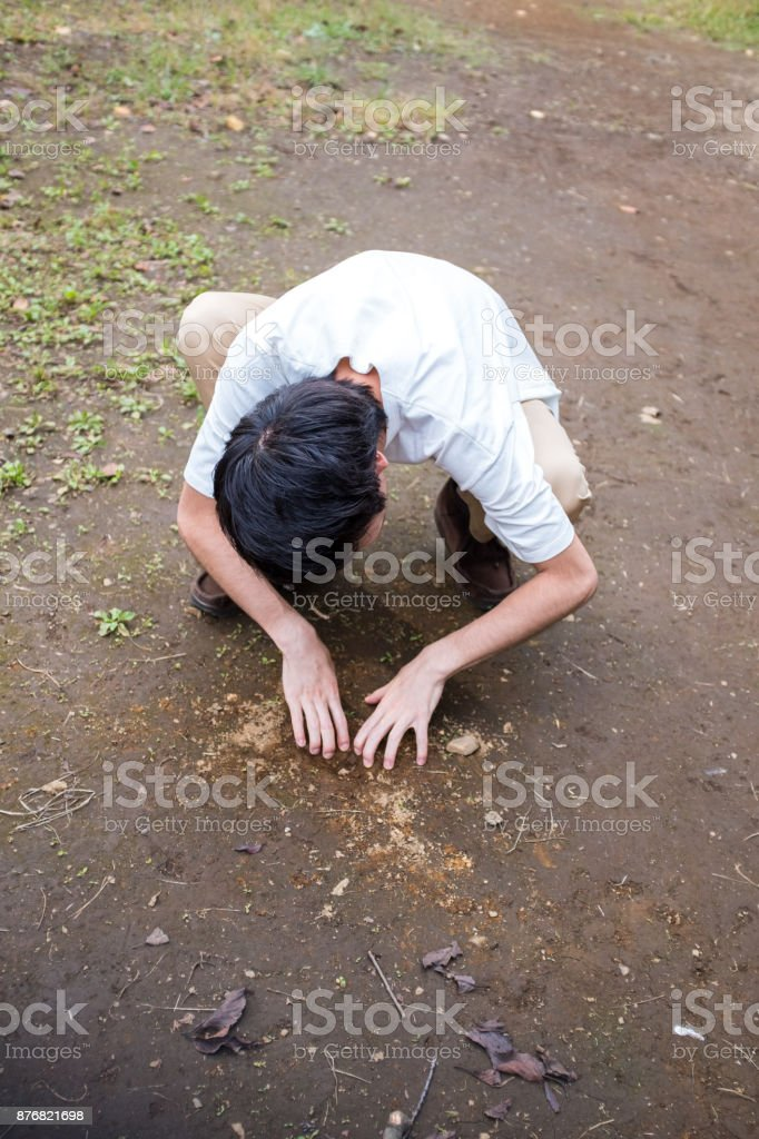 Man digging the ground with bare hands stock photo
