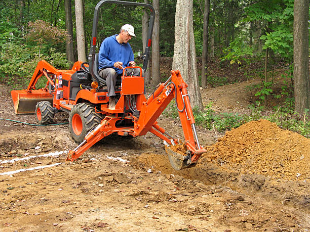 Man digging trench with backhoe stock photo