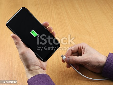 Man disconnect the charging cable from the smartphone. Full charge visible on screen