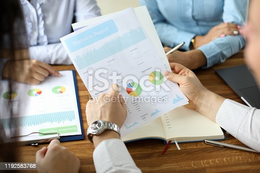 Close-up of financial statement in businessman hands. Biz team speaking about statistics report with graphs, charts, diagram. Business meeting and teamwork concept