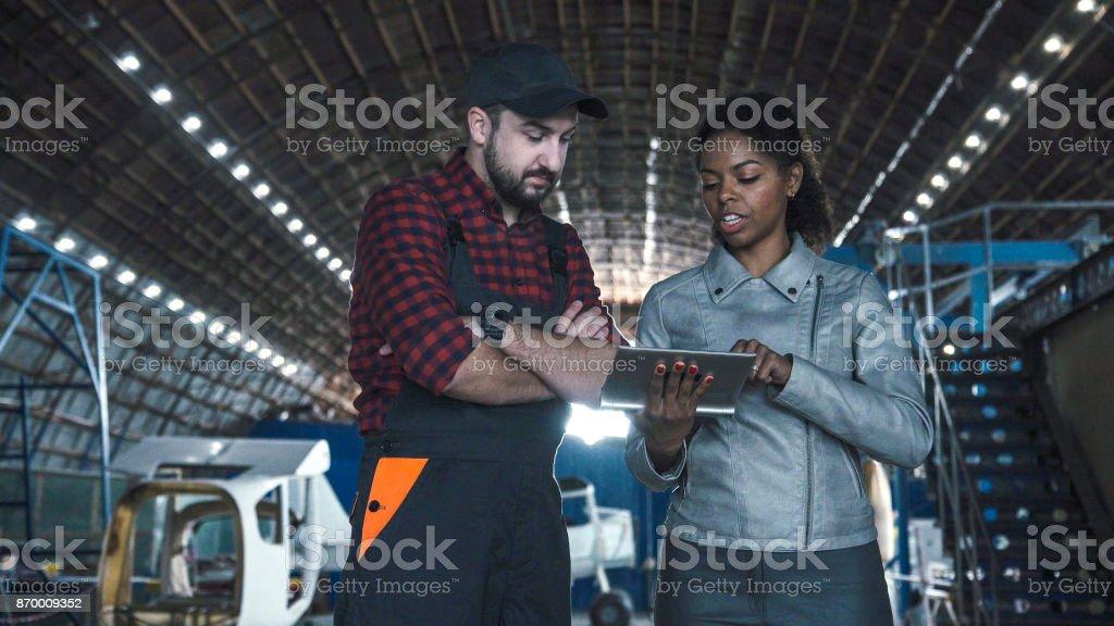 Mann im Flugzeughangar mit Frau diskutieren – Foto