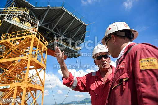 Chonburi,  Thailand - November 25, 2013 - NOV 25 : Workers of oil and gas rig standing in front of the rig in rig maintenance operation at shipyard on Nov 25, 2013
