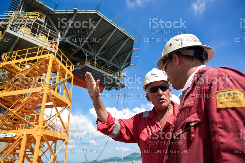 Man discussing in oil rig maintenance at shipyard stock photo