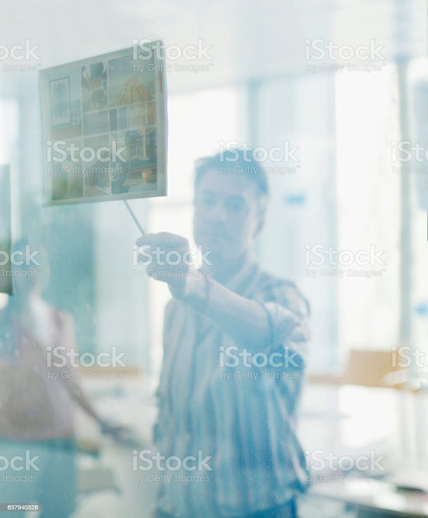 Man discussing layout diagram through translucent glass wall – Foto