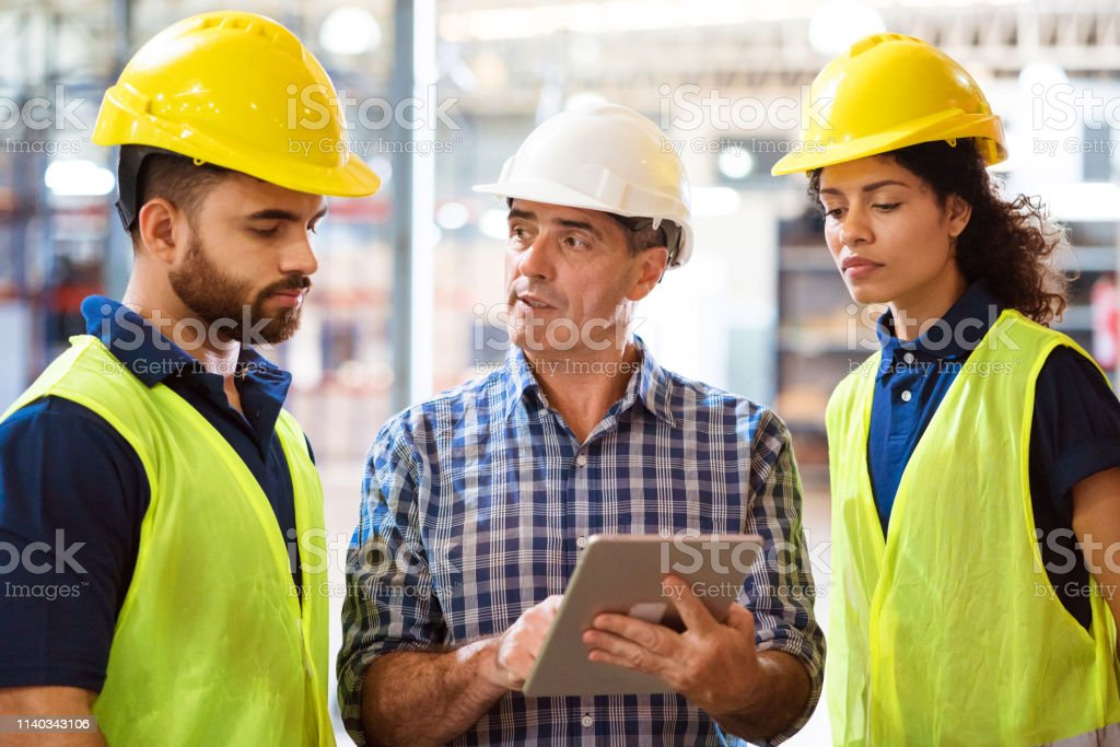 Man discussing over digital tablet with colleagues Foreman discussing over digital tablet with colleagues in factory. Engineers are working together in manufacturing company. They are wearing hardhats. 20-24 Years Stock Photo