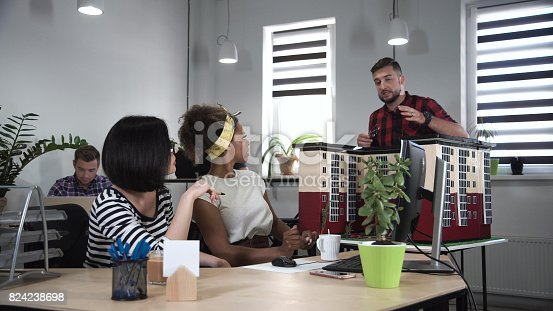 487670635istockphoto Man discussing with two women in office 824238698