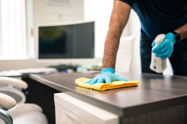 Man disinfecting an office desk stock photo