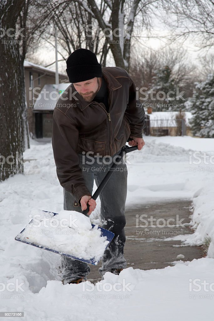 Man dissing out the snow in the street royalty-free stock photo