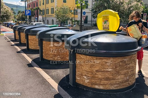 GARDA, ITALY - AUGUST 08, 2019: A man distributes garbage in the different containers