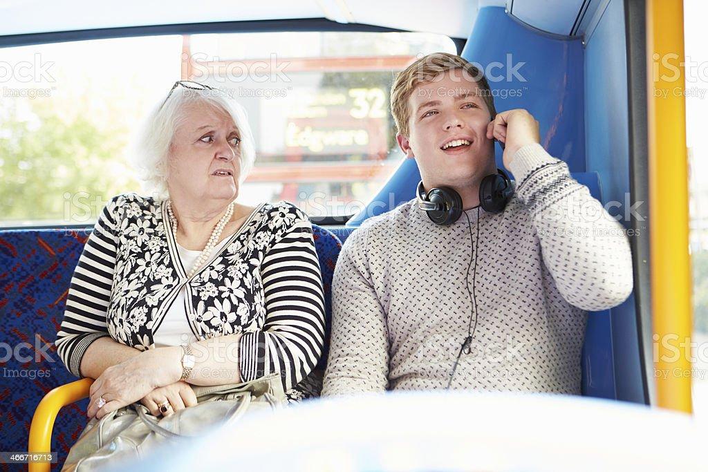 Man disturbing passengers on bus journey with phone call stock photo