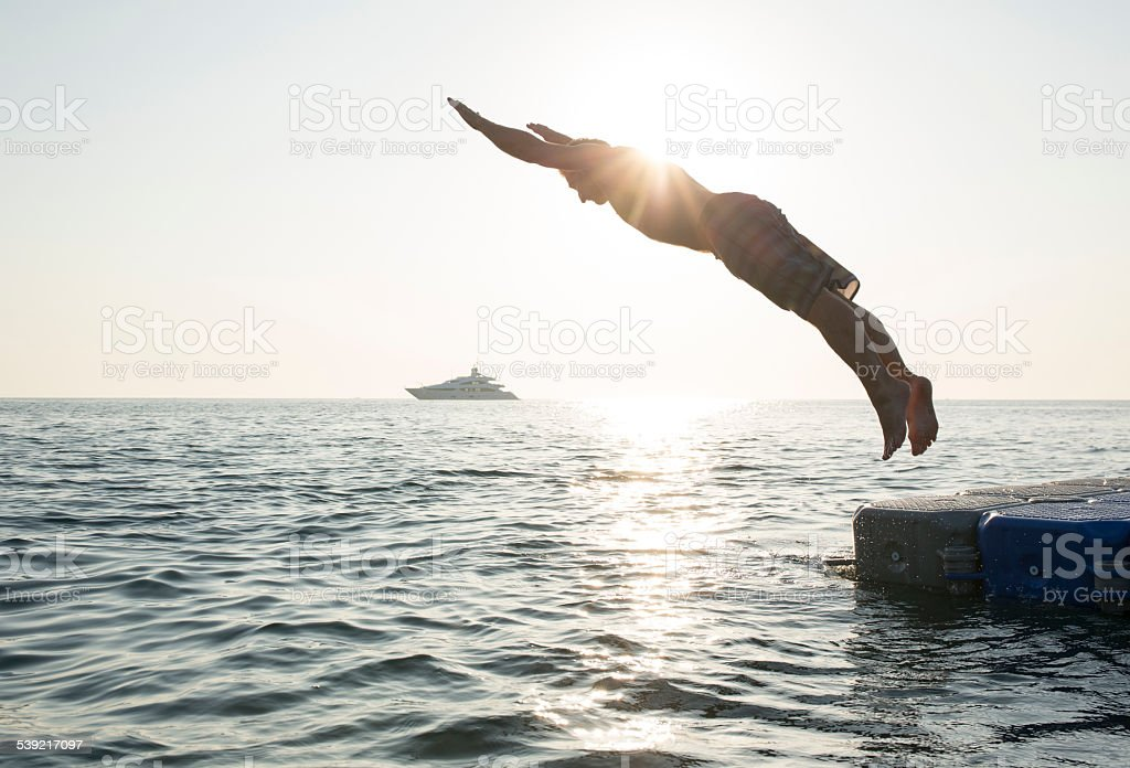 Man dives into tranquil sea, from pier, boat stock photo